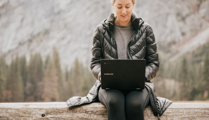 Woman sitting on log with laptop